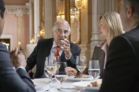 Gesturing : Four business people sitting at restaurant table talking