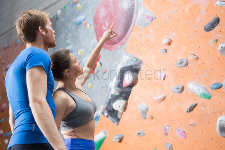 Rock wall : Friends discussing by climbing wall in crossfit gym