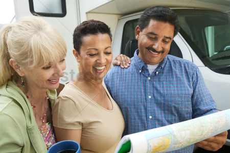 On the road : Friends studying road map beside motor home