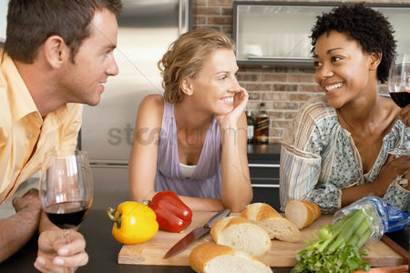 Smiling : Friends talking while preparing dinner portrait