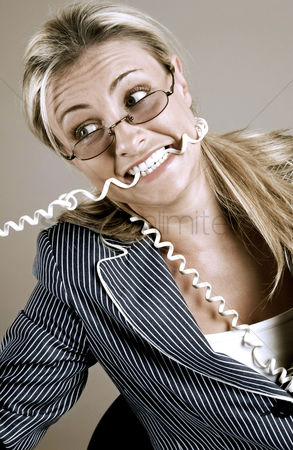 Rage : Frustrated businesswoman biting the phone cord