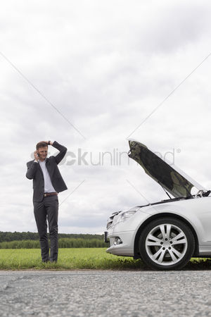 On the road : Frustrated young businessman using cell phone near broken down car at countryside