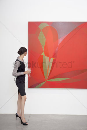 Interior background : Full length of a woman looking at painting in art gallery