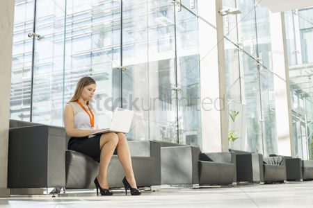 Internet : Full-length of businesswoman using laptop at office lobby