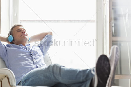 40 44 years : Full-length of relaxed middle-aged man listening to music at home