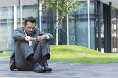 Business suit : Full length of sad businessman sitting on path outside office