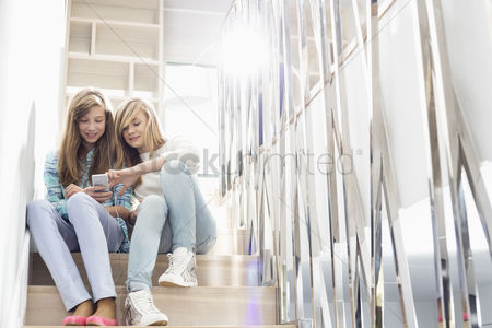 Steps : Full-length of sisters listening to music on stairway