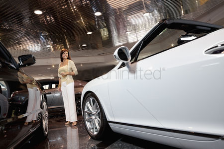 Show : Full-length of smiling woman standing in car showroom