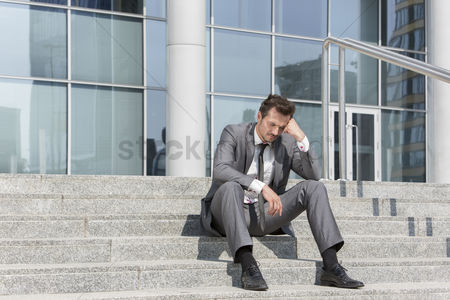 Worry : Full length of stressed businessman sitting on steps outside office