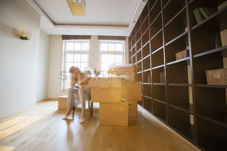 Pressure : Full-length of stressed woman sitting by cardboard boxes in new house