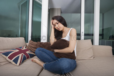 Asian : Full length of worried young woman sitting on sofa