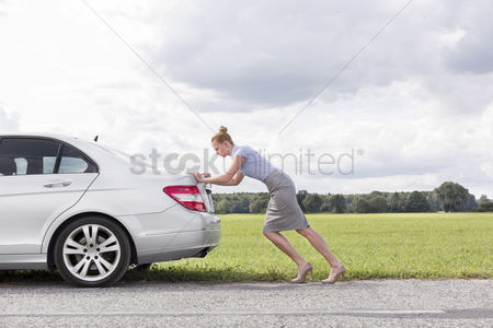 Land : Full length side view of businesswoman pushing broken down car at countryside