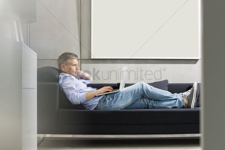 40 44 years : Full-length side view of middle-aged man using laptop while lying on sofa