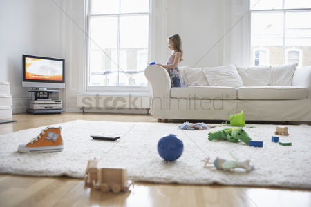 Flat : Girl  5-6  watching television toys on floor in foreground