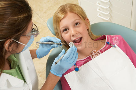 Expertise : Girl  7-10  having teeth examined at dentists