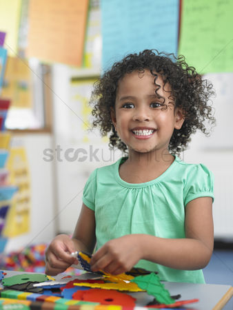 Satisfaction : Girl assembling  puzzles in classroom portrait