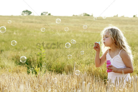 Children playing : Girl blowing bubbles in the field