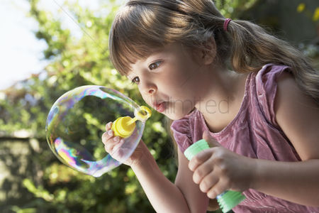 Blowing : Girl blowing soap bubbles in backyard close up