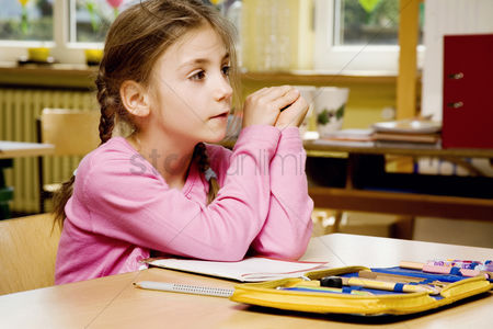 School children : Girl daydreaming in the classroom