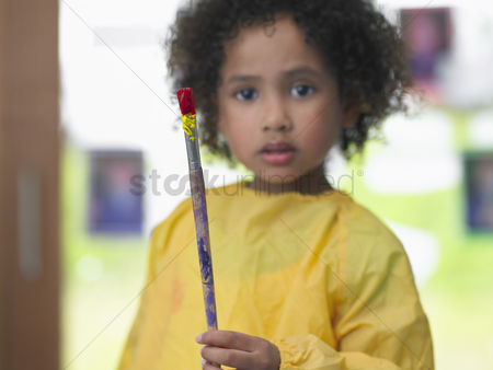 Paint brush : Girl holding paint brush in art class portrait