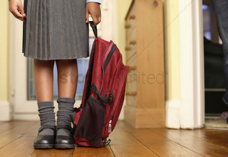 School children : Girl in school uniform holding school bag