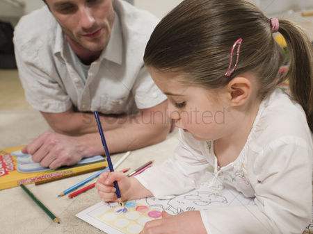 Offspring : Girl on floor coloring with father