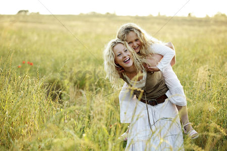 Grass : Girl on woman s back
