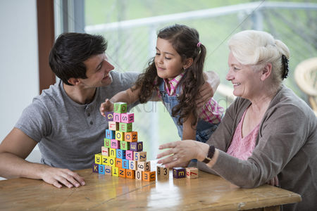 Czech republic : Girl playing with alphabet blocks by father and grandmother at table in house