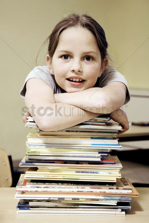 Smiling : Girl resting on a stack of books