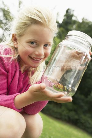 Posed : Girl showing insect in jar