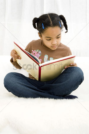 School children : Girl sitting on the bed reading book