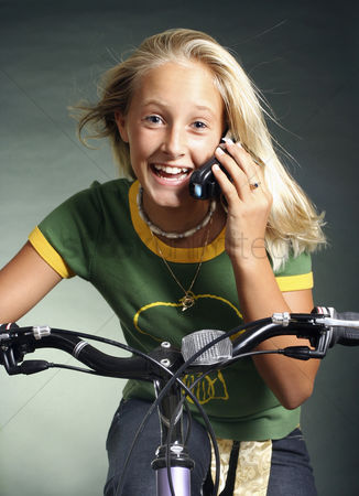 Lively : Girl talking on the mobile phone while cycling