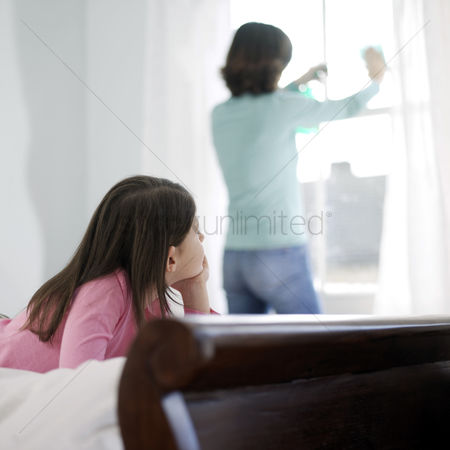 Daughter : Girl watching her mother cleaning the window