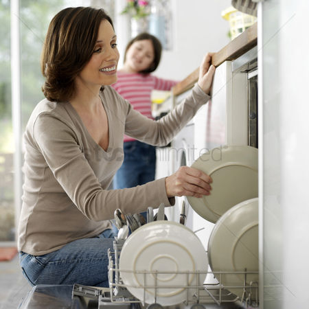 Bonding : Girl watching her mother keeping the dishes in the dishwasher