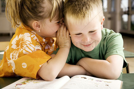Young boy : Girl whispering something into boy s ear