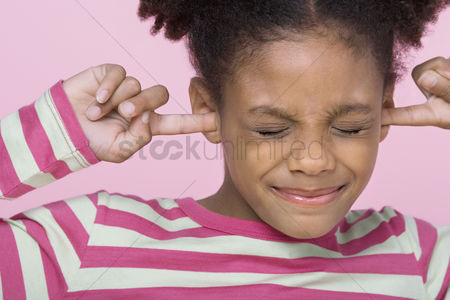 Pre teen : Girl with eyes closed putting fingers in ears close-up
