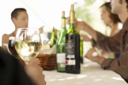 Gesturing : Glass of white wine on table surrounded by group of people