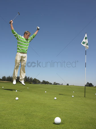 Arm raised : Golfer cheering on putting green