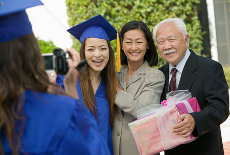 University : Graduate videotaping other graduate with mother and grandfather outside