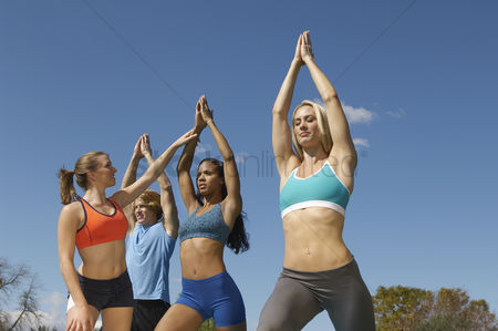 Arm raised : Group exercising with instructor in park