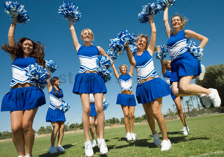 Pitch : Group of cheerleaders rising pom-poms jumping on football field