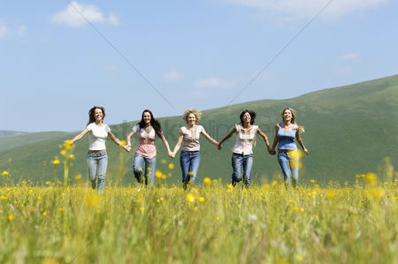 Denim : Group of friends running through mountain field front view