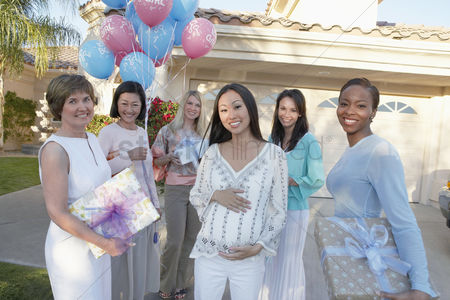 Women group outside : Group of friends with gifts for baby shower outside house