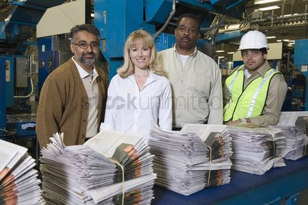 Pile : Group of people working in newspaper factory portrait
