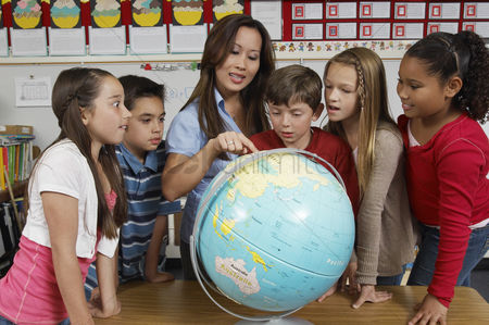 Teacher : Group of pupils and teacher looking at the globe