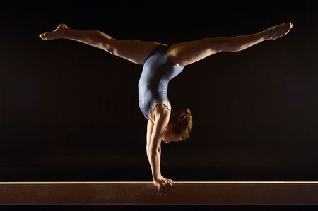 Black background : Gymnast  13-15  doing split handstand on balance beam side view
