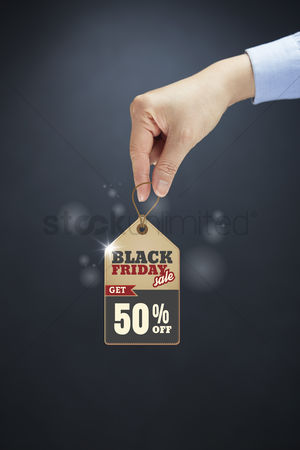 Grasp : Hand holding a black friday sale tag
