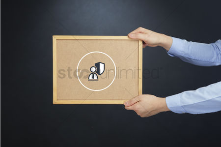 Cork board : Hand holding a board with protection concept