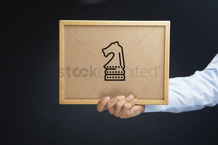 Cork board : Hand holding a cork board with strategy concept