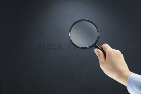Magnifying glass : Hand holding a magnifying glass